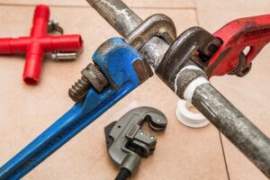 Plumbers wrenches around pipe for Houston commercial plumbing repair